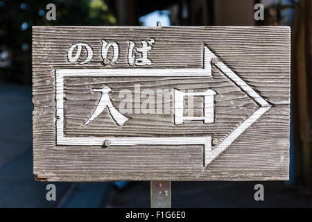 Iwakuni, Japan. Wooden board sign pointing to the entrance of the cable car station, (platform). Sign is in kanji - Stock Photo