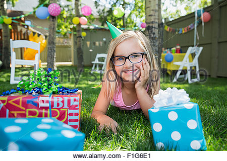 Portrait smiling girl birthday party hat gifts grass - Stock Photo