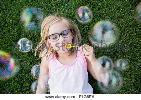 Overhead view blonde girl with eyeglasses blowing bubbles - Stock Photo