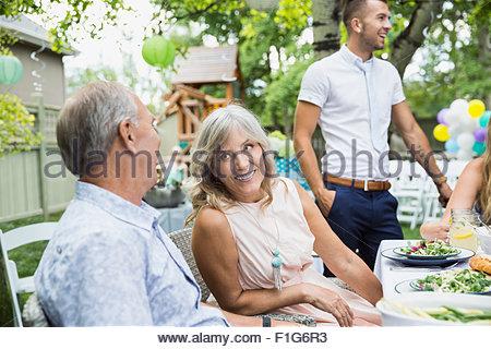 Smiling senior couple enjoying garden party lunch - Stock Photo