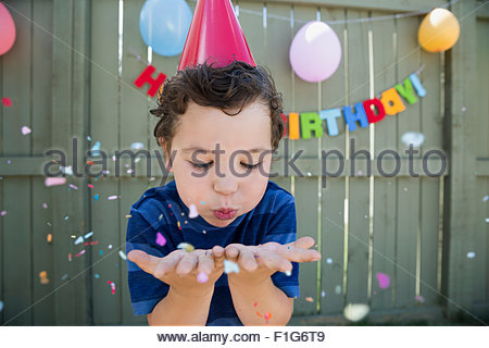 Boy wearing birthday party hat blowing confetti - Stock Photo
