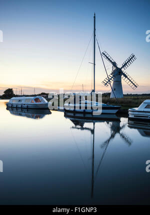 Sailing boats moored on riverbank at sunrise in countryside landscape - Stock Photo