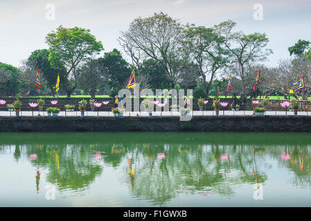 Hue Vietnam citadel, tourists walk alongside one of many lakes inside the Imperial Citadel in Hue, central Vietnam. - Stock Photo