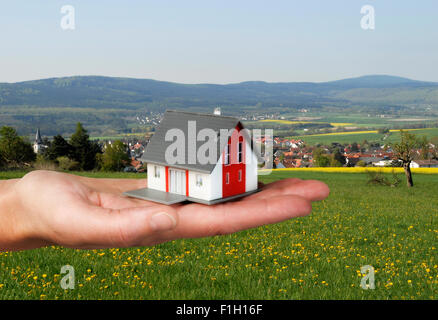 House on a hand in front of landscape - Stock Photo