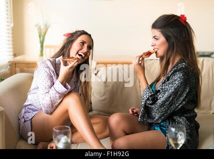 Two young women having girls night in, sitting on sofa, eating and laughing - Stock Photo