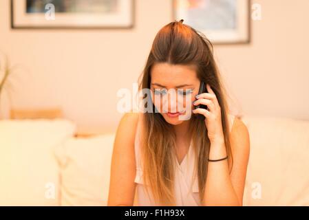 Young woman having telephone conversation, crying - Stock Photo