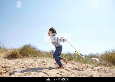 Young boy flying kite on beach - Stock Photo