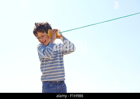 Young boy, holding cup and string telephone to ear - Stock Photo