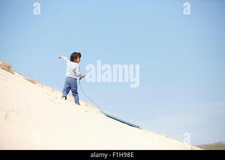 Young boy with sledge on sandy hill - Stock Photo