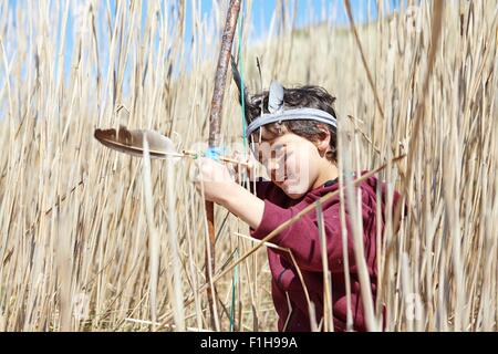 Young boy wearing fancy dress, holding home-made bow and arrow - Stock Photo