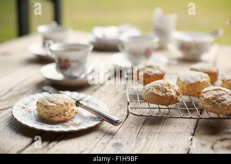 Table with fresh baked scones and afternoon tea - Stock Photo