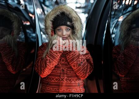 Mid adult woman wearing coat with furry hood, portrait - Stock Photo