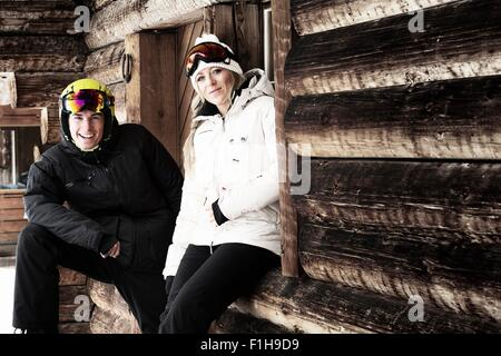Man and woman by chalet, portrait - Stock Photo