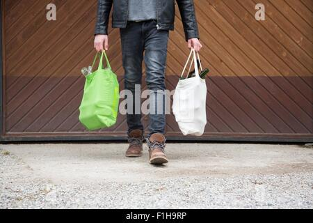 Teenage boy carrying reusable shopping bags full of empty bottles for recycling - Stock Photo