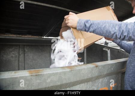 Teenage boy emptying paper waste to recycling bin - Stock Photo