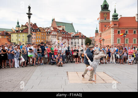 Oldie breakdance show, tourists watching street dance performance in Old Town square in Warsaw, Poland. Old couple - Stock Photo