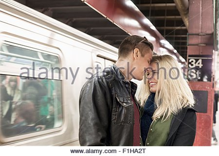 Romantic young couple on New York City subway platform,  New York, USA - Stock Photo