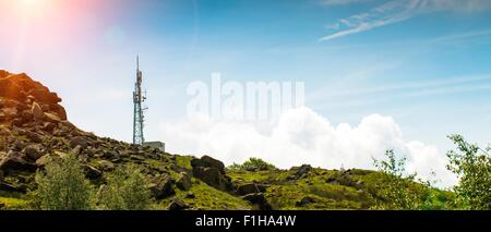 Low angle panoramic view of cell phone mast on hill, UK - Stock Photo
