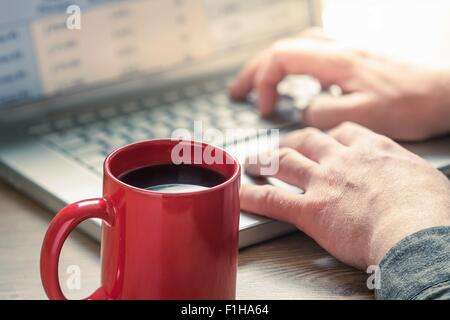 Hands of man typing on laptop at desk - Stock Photo
