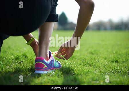 Cropped rear view of mature woman tying trainer laces in park - Stock Photo