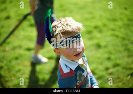 Portrait of  young boy wearing headband with feathers - Stock Photo