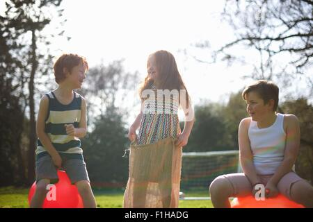 Young children on inflatable hopper and standing in sack, ready for race - Stock Photo