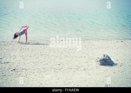 Mid adult woman, beside lake, in yoga position - Stock Photo