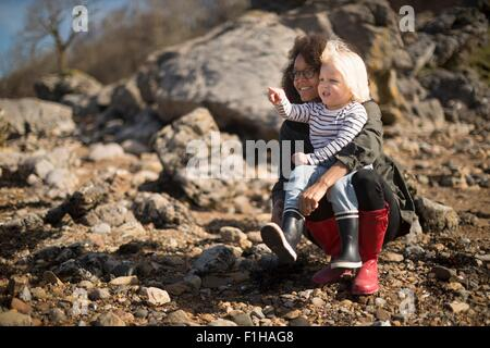 Mother and son crouching on rocks - Stock Photo