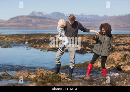 Father holding son by Loch Eishort, Isle of Skye, Hebrides, Scotland - Stock Photo