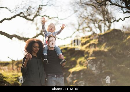 Family on walk, father carrying son on shoulders - Stock Photo