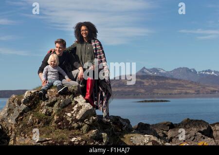 Family on rocks, Loch Eishort, Isle of Skye, Scotland - Stock Photo