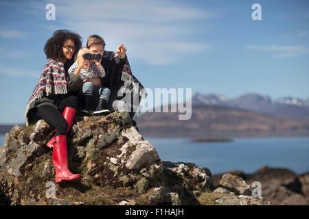 Family sitting on rocks, boy using binolculars - Stock Photo