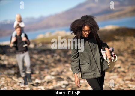Woman walking with man and child in background - Stock Photo