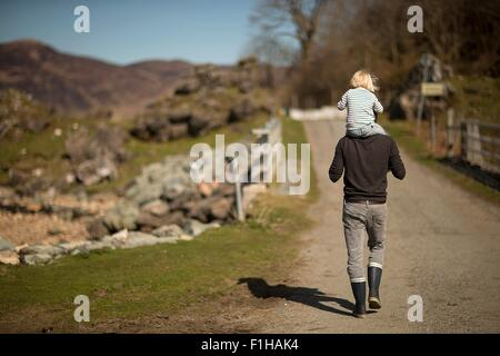 Father carrying son on shoulders, walking on path, rear view - Stock Photo
