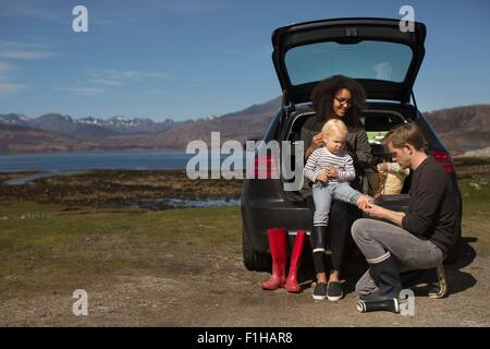 Parents helping son change shoes, Loch Eishort, Isle of Skye, Hebrides, Scotland - Stock Photo