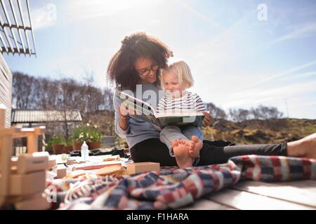 Mother reading book to son on picnic blanket - Stock Photo