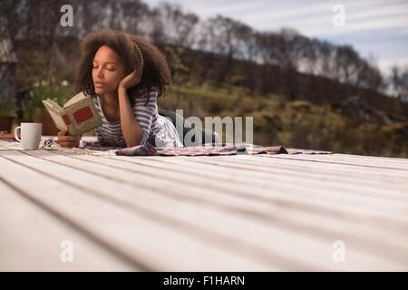 Mid adult woman lying down, reading book - Stock Photo