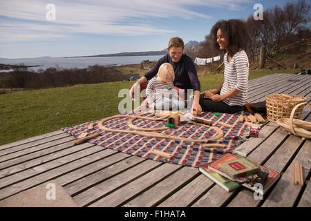 Boy and parents playing with toy train on wooden decking - Stock Photo