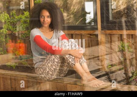 Mid adult woman sitting looking through window, portrait