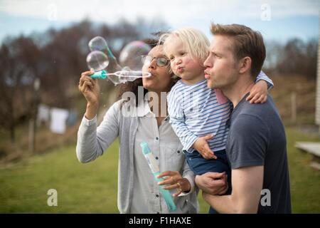 Mother blowing bubbles, father holding son - Stock Photo