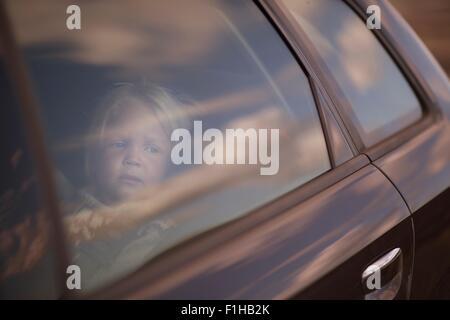 Boy looking through car window - Stock Photo