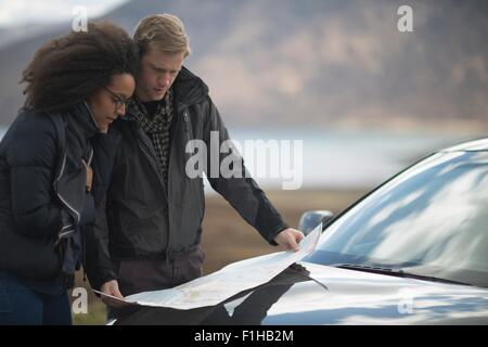 Mid adult couple by car with map - Stock Photo
