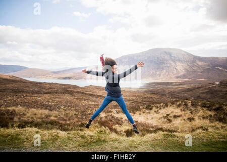 Mid adult woman in mountains doing star jump, Isle of Skye, Hebrides, Scotland - Stock Photo