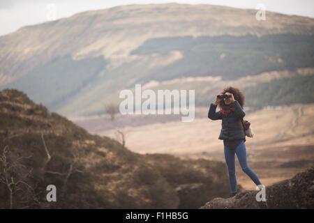 Woman using binoculars, Fairy Pools, Isle of Skye, Hebrides, Scotland - Stock Photo