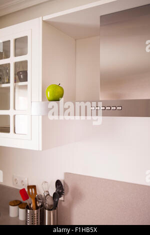 Green apple symbolizing cleanliness in a modern white kitchen with kitchen stuff. - Stock Photo