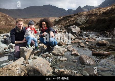Family by stream, Fairy Pools, Isle of Skye, Hebrides, Scotland - Stock Photo