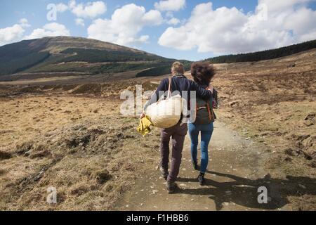 Couple hiking on path in hills, Fairy Pools, Isle of Skye, Hebrides, Scotland - Stock Photo