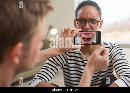 Man holding smartphone in front of woman's mouth - Stock Photo