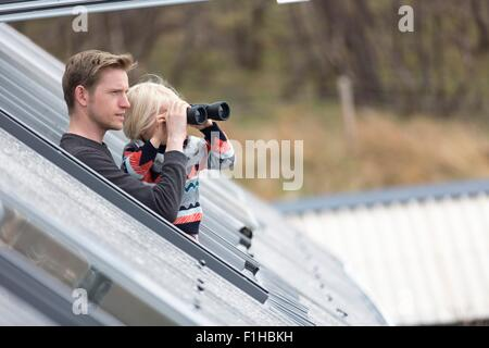 Father and son looking through rooflight, boy using binoculars - Stock Photo