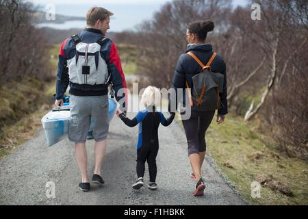 Family walking on country road holding hands, rear view - Stock Photo
